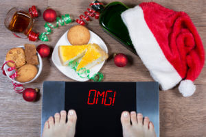 "Female feet on digital scales with sign ""omg!"" surrounded by Christmas decorations, bottle, glass of alcohol and sweets. Concept of unhealthy lifestyle."